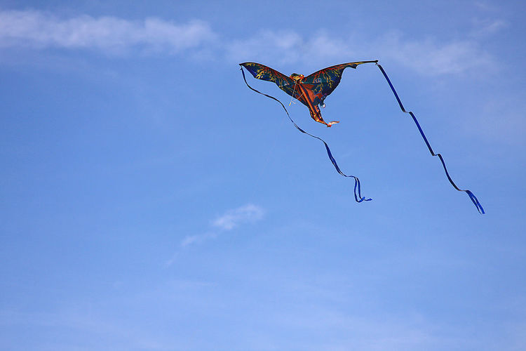 Low angle view of kite flying against sky on sunny day