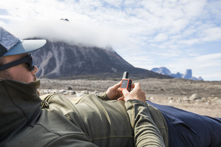 Rear view of man using mobile phone against sky