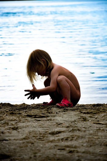 Rear view of shirtless boy playing in water at beach