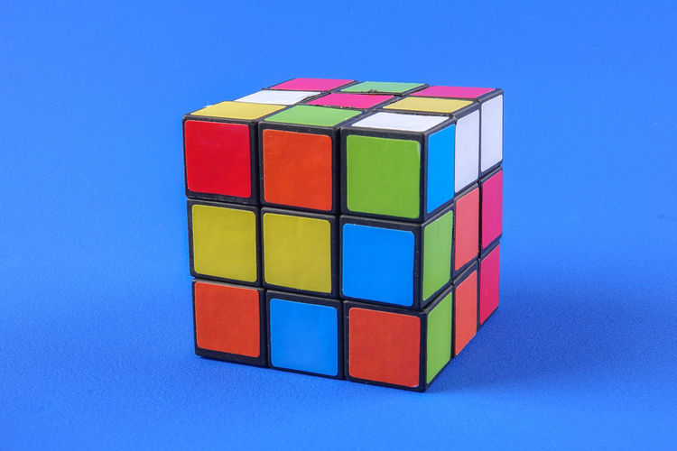 RUBIK'S CUBE , CREATIVITY TOY Creativity Rubik Cube Block Blue Blue Background Close-up Colored Background Cube Shape Cut Out Design Geometric Shape Indoors  Intelligence Large Group Of Objects Multi Colored No People Red Rubik Shape Single Object Still Life Studio Shot Toy Toy Block