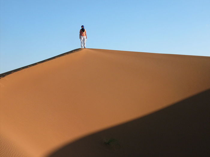 Low angle view of woman standing on sand dune