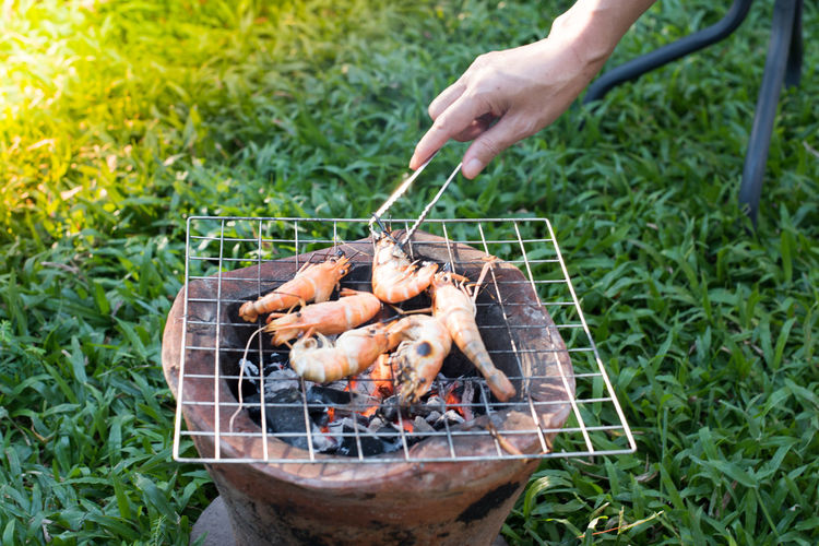 Cropped hand preparing shrimp on barbecue grill