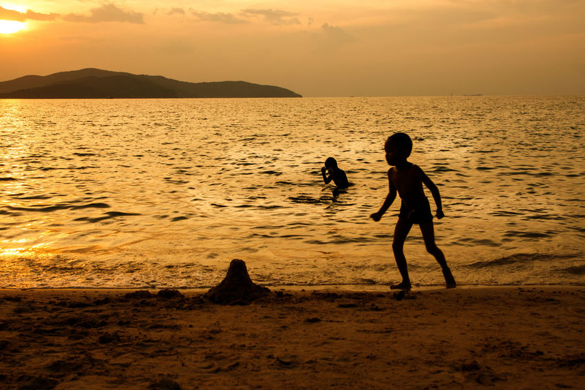 silhouette of people at the beach,The beauty of natural light at sunset. Sky Water Sunset Sea Beach Beauty In Nature Land Scenics - Nature Two People Togetherness Lifestyles Real People Orange Color Nature Men Horizon Over Water Child Leisure Activity Tranquility Positive Emotion Outdoors Silhouette Happiness Happy People Holiday Relaxing Children Women Man Romantic Orange Clouds And Sky Love Family Summer Sunrise Boy Freshair Freedom Fun