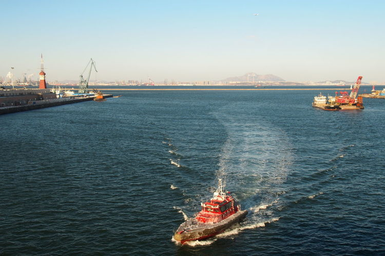 High Angle View Of Tugboat On Sea Against Clear Sky