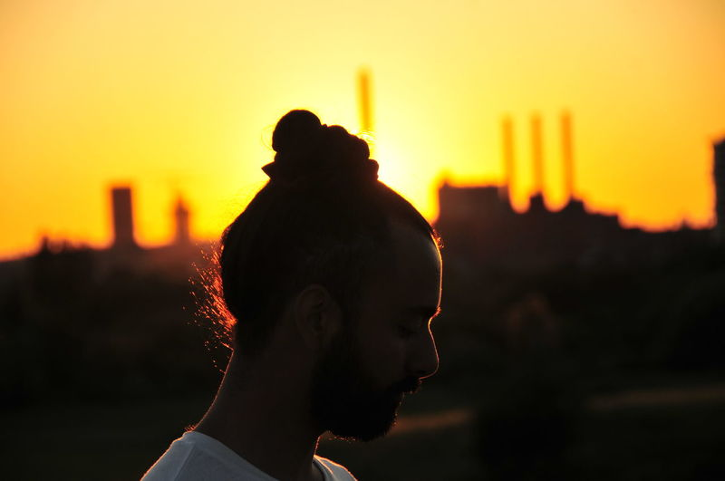 Close-up of man with hair bun against sky during sunset