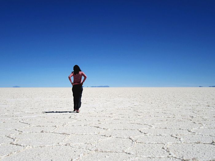 Rear View Of Mid Adult Woman Standing On Arid Landscape Against Clear Blue Sky During Sunny Day