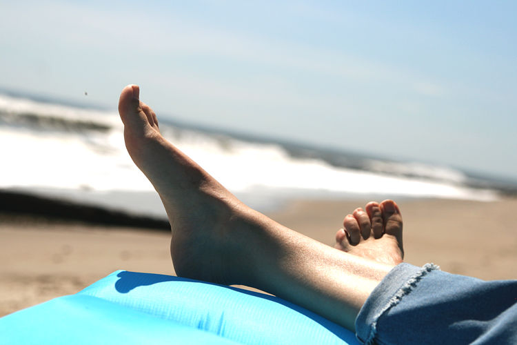Low section of person lying on beach bare feet
