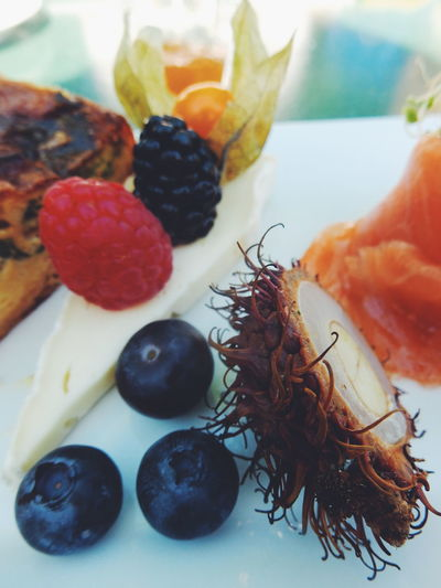 Close-up of fruits and smoked salmon in plate