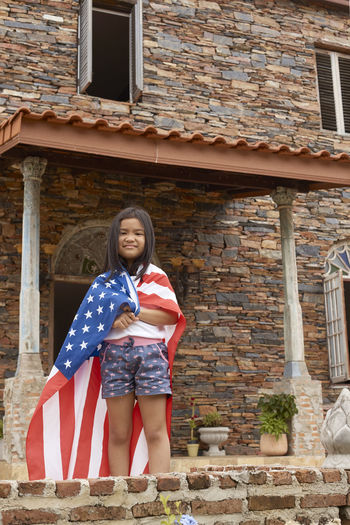 Cute girl with american flag standing against house