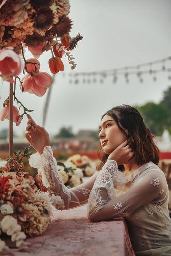 Woman looking at flowering plants against sky