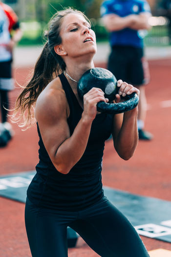 Woman lifting kettlebell on running track