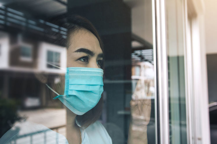 Close-up of woman wearing mask seen through window