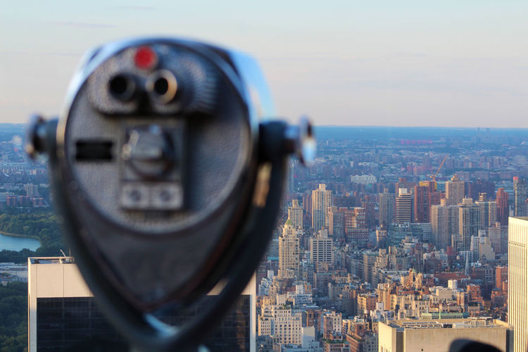 Coin-operated binoculars against cityscape