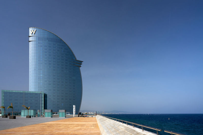 View of building by sea against clear blue sky