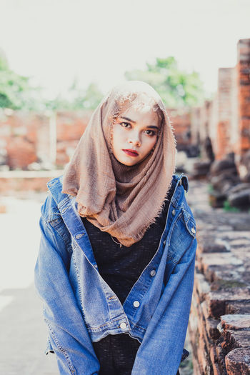 Portrait Of Young Woman Wearing Hijab And Denim Jacket Standing In City