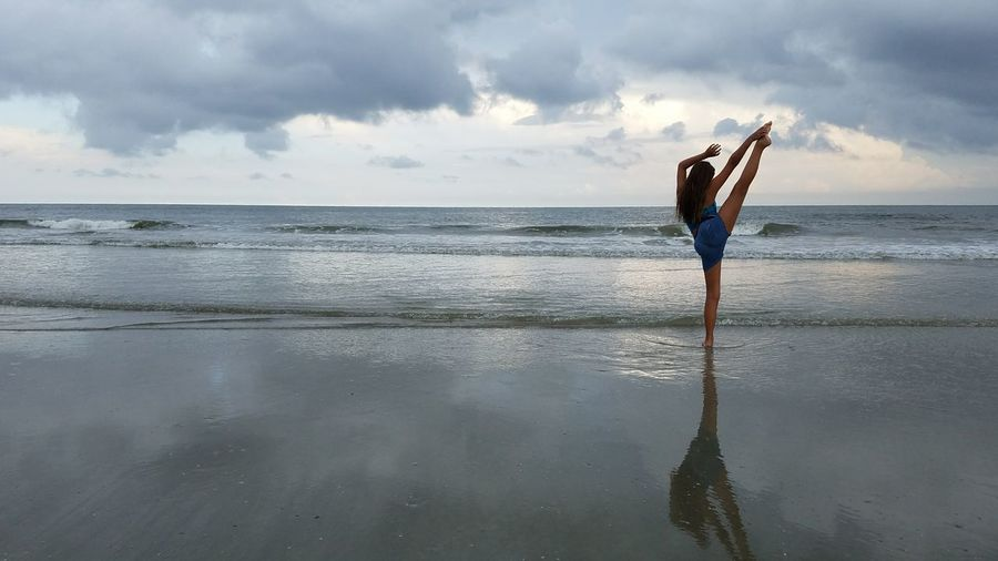 Rear view of woman exercising on shore at beach