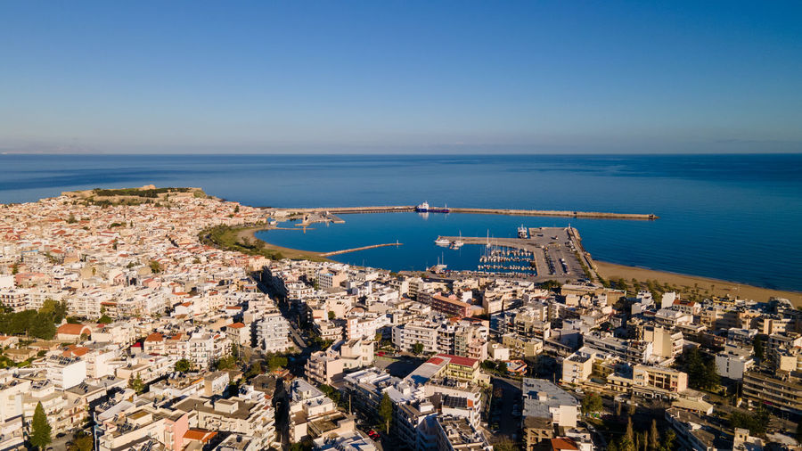 High angle view of city by sea against clear sky