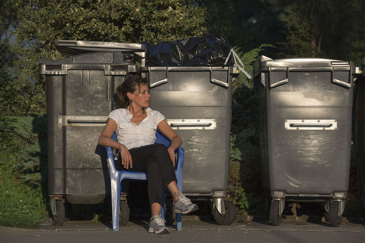 Young woman sitting on chair by wheeled garbage cans