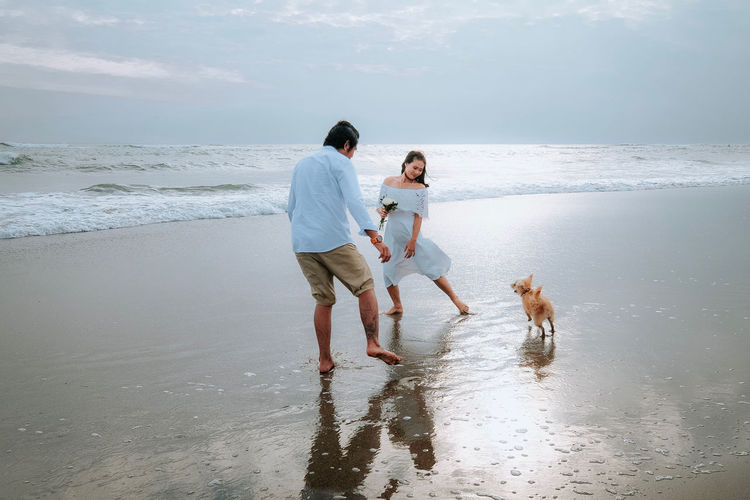 Man with woman and dog on beach