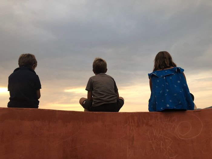 Rear view of people looking at sunset sky