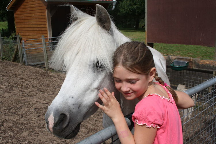 Close-up of smiling girl with horse