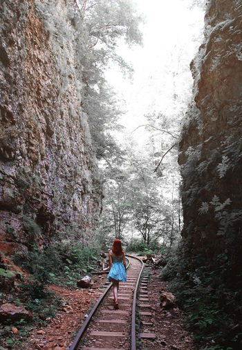 Rear view of woman standing on railway track in mountains