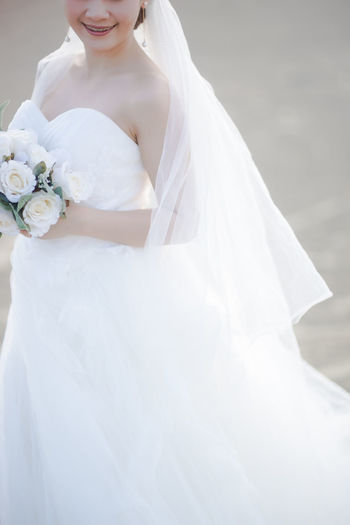 Midsection Of Bride Holding Bouquet While Standing On Road