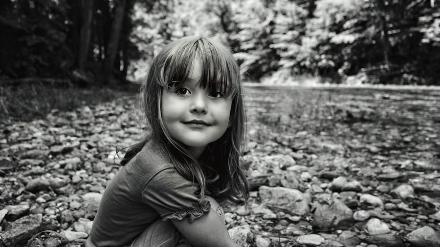 Portrait Of Smiling Girl Sitting On Stones In Forest