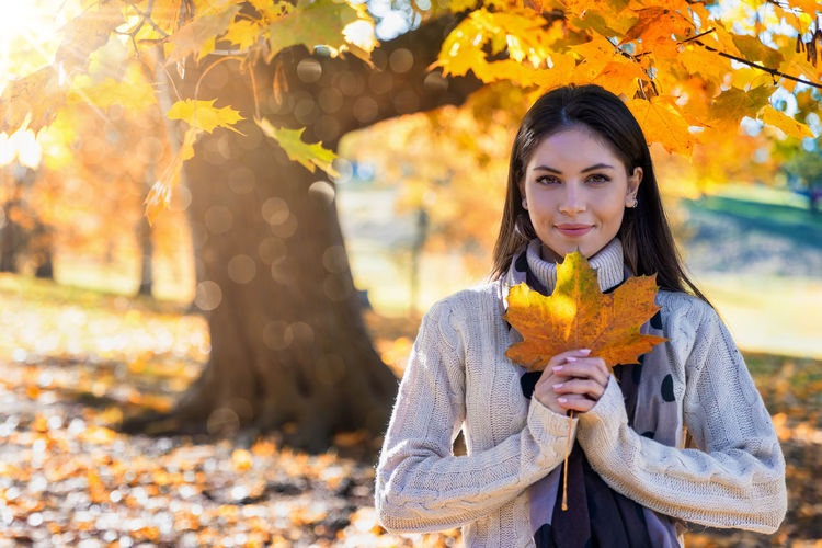 Autumn concept: attractive woman holds a colourful leaf in the park with falling leaves and golden sunshine Autumn One Person Leaf Plant Part Portrait Change Looking At Camera Young Adult Front View Real People Standing Young Women Leisure Activity Tree Waist Up Beautiful Woman Day Yellow Leaves Hair Hairstyle Holding Focus On Foreground Park Concept Colourful Tree October Autumn Season  Outdoors Golden Sun Sunlight