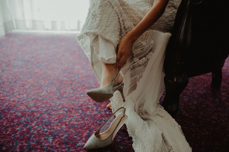 Low section of bride wearing sandals while sitting on chair