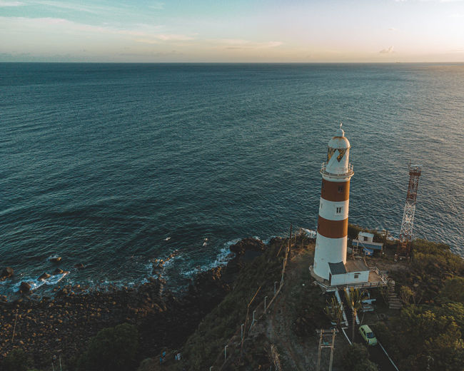 High angle view of lighthouse amidst sea against sky