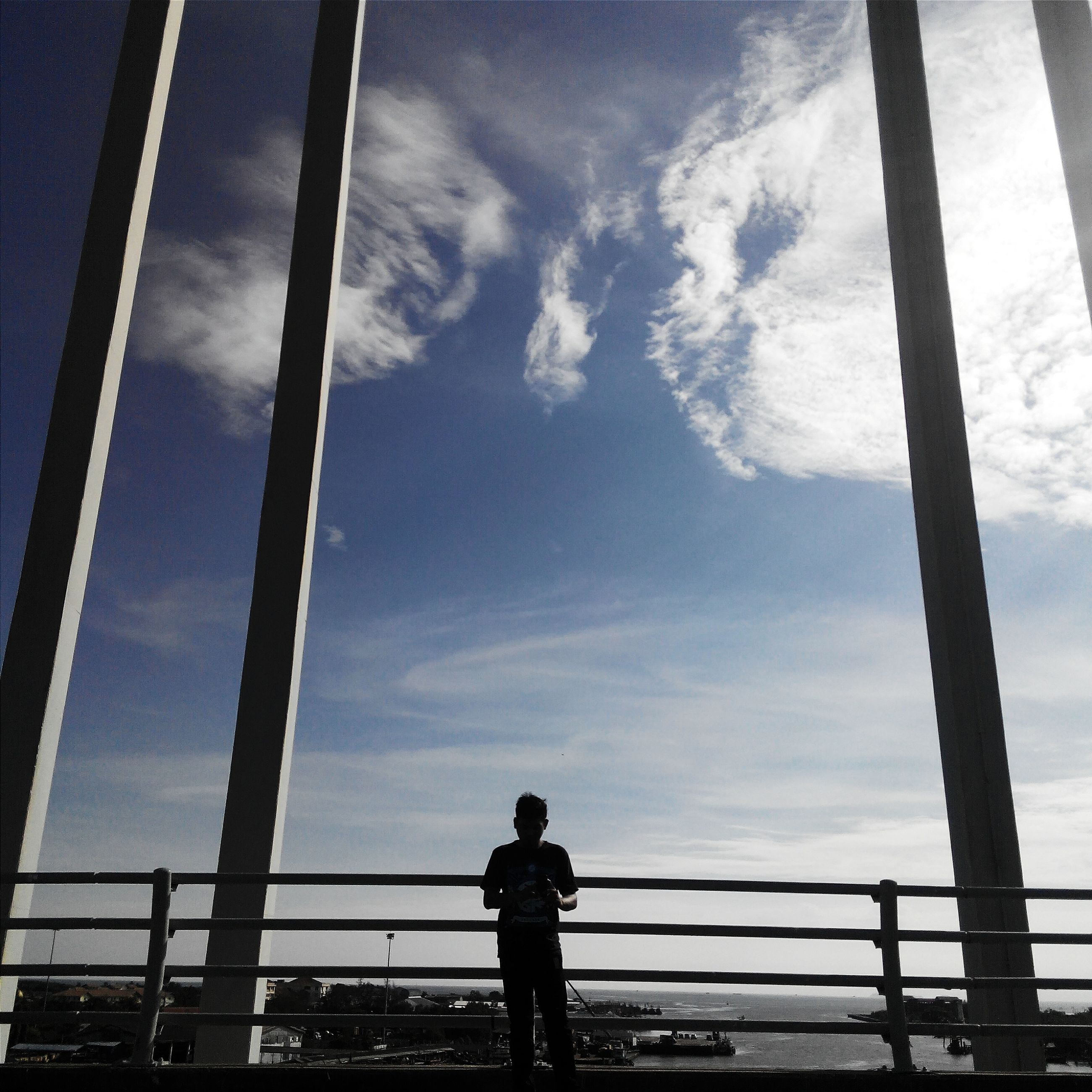 sky, railing, low angle view, cloud - sky, built structure, silhouette, standing, architecture, lifestyles, men, cloud, leisure activity, day, outdoors, rear view, bridge - man made structure, street light