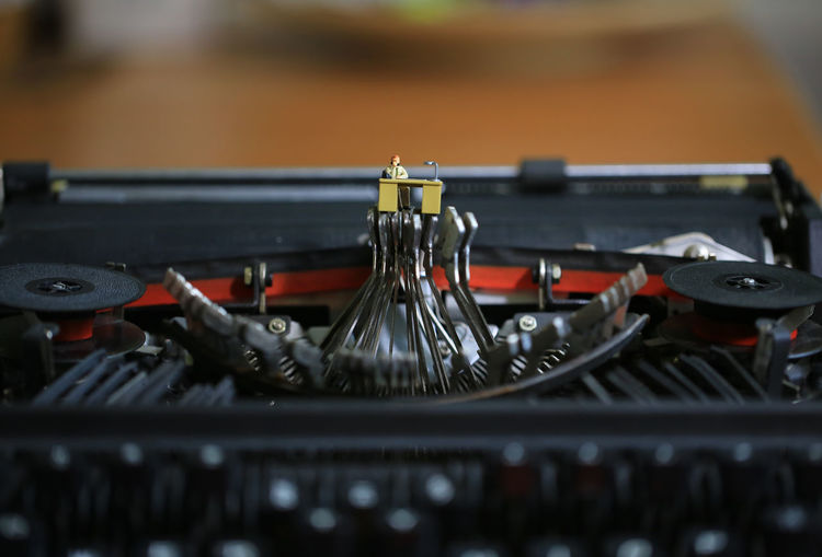 man busy on keyboard Tiny Typewriter Machinery Electrical Equipment No People Surreal Worker Working Desk Help Desk Office Technology Selective Focus Indoors  Retro Styled Busy Typography Keyboard