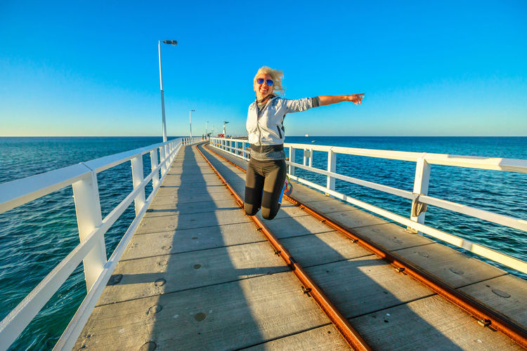 Western Australia travel freedom concept. Happy caucasian woman jumping at Busselton jetty in Busselton, Western Australia. Female jumper over iconic wooden pier in WA, Australia. Steam Train Train Australia Jetty Busselton Busselton Jetty Busselton Western Australia Busseltonjetty Western Australia Beach Station Travel Pier Tourist Railway Railway Track Sea Transportation Tourist Attraction  Landmark Sunset Woman Girl Water One Person Sky Full Length Railing Horizon Leisure Activity Horizon Over Water Real People Young Adult Nature Beauty In Nature Standing Lifestyles Scenics - Nature Young Women Sunlight Fashion Outdoors