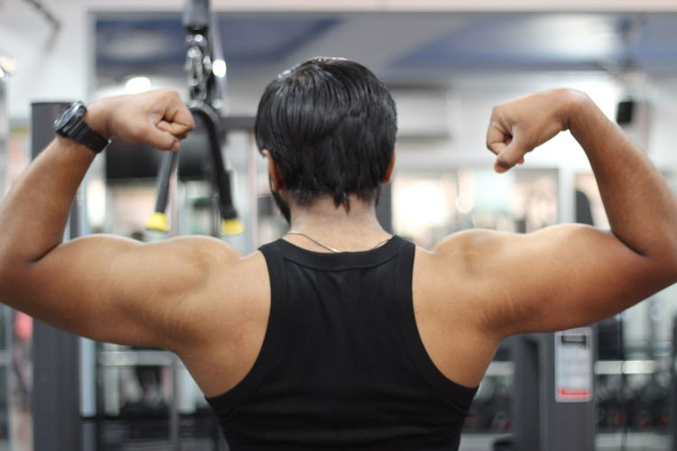 Rear view of man flexing muscles at gym