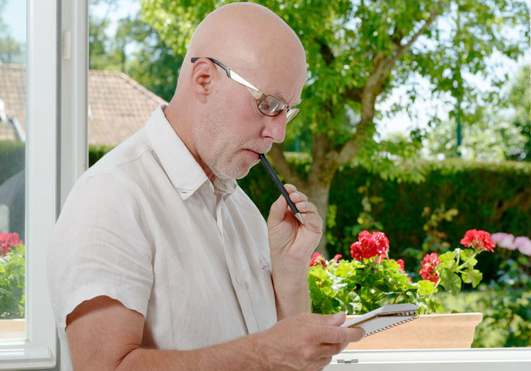 Thoughtful Man Holding Diary And Pen While Standing At Home