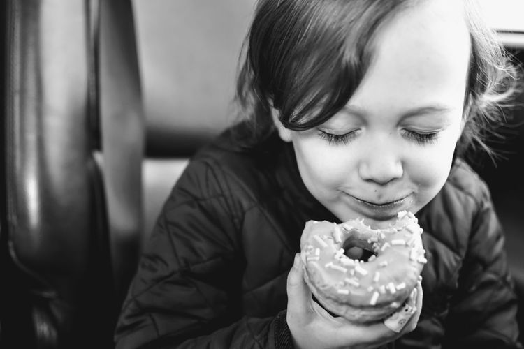 Close-Up Of Cute Boy Eating Donut
