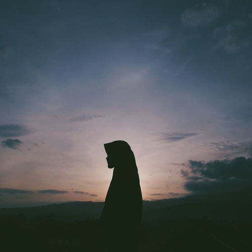 Silhouette woman wearing hijab standing against sky during sunset