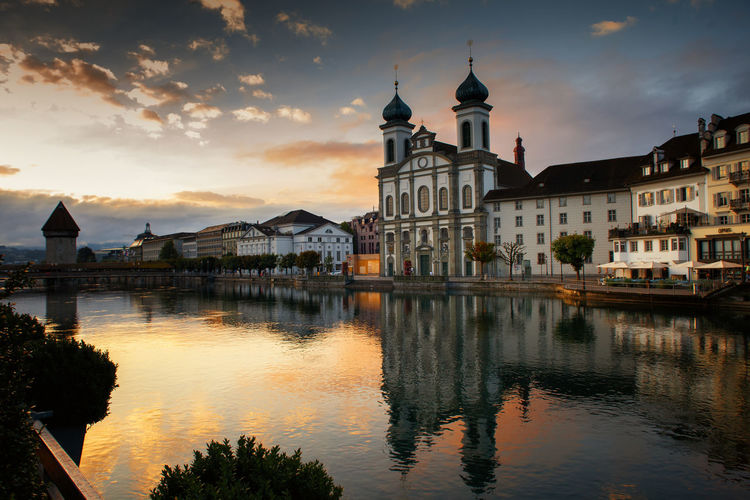 Reflection of buildings and church in river against cloudy sky at sunset