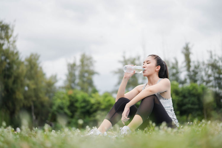 Young woman drinking glass on field