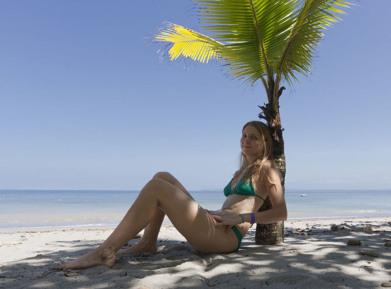 Young woman leaning against palm tree at beach - Punta Leona, Costa Rica Beach Bikini Blond Hair Carefree Costa Rica Getting Away From It All Happy Idyllic Leisure Activity Lifestyles Long Hair One Woman Only One Young Woman Only Palm Tree Punta Leona Relaxation Sand Sea Sitting Tropical Tropical Climate Tropical Paradise Vacations Woman Young