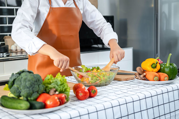 Midsection of man with vegetables in kitchen