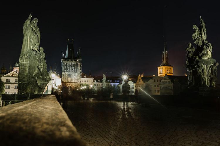 Statue of illuminated city at night