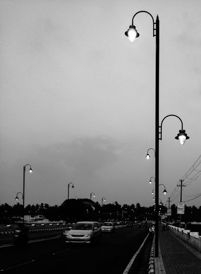 Road Side Photography Cars And People Street Lamp Hazy Shot Evening Light Street_lights Saligao, Goa On The Road Travel Photography Black And White Photography Monochrome City Lights City Life Urban Landscape City Street