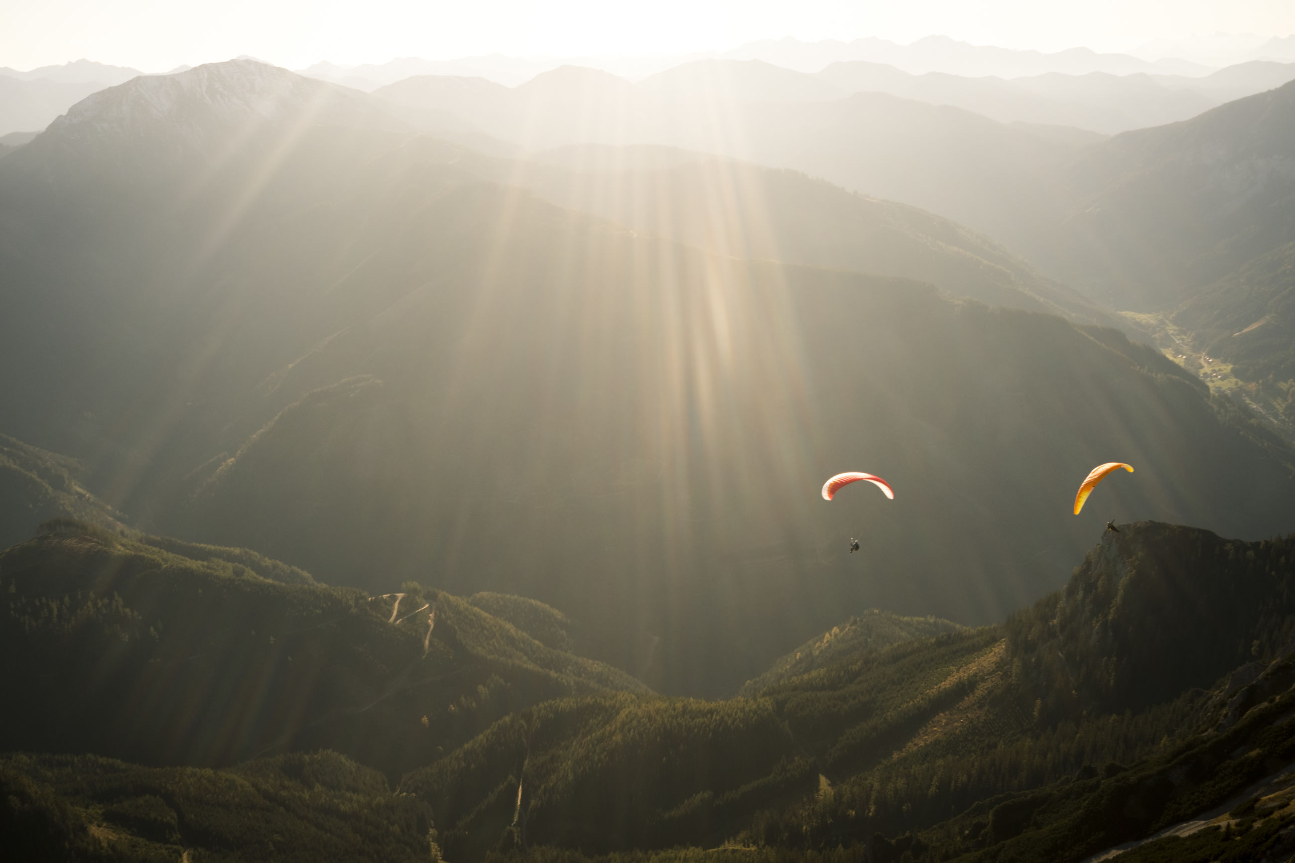 mountain, adventure, beauty in nature, sunlight, mountain range, parachute, sky, scenics - nature, sunbeam, paragliding, extreme sports, nature, tranquility, lens flare, tranquil scene, leisure activity, sun, environment, day, sport, freedom, outdoors, bright
