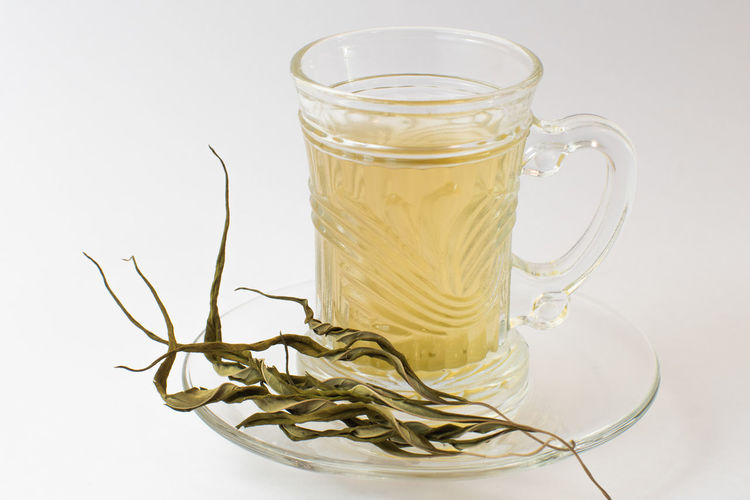 Close-up of glass of tea against white background