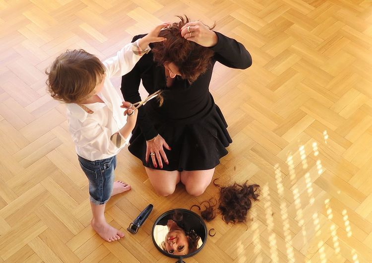 High angle view of child cutting hair of woman