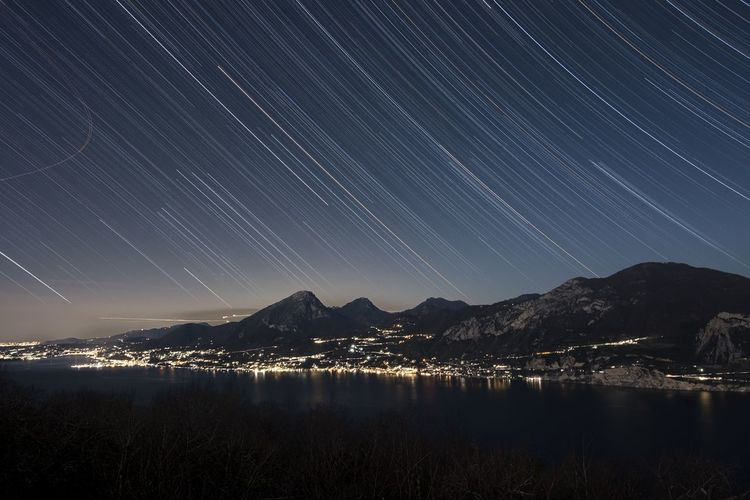 Light trails above lake and mountains at night