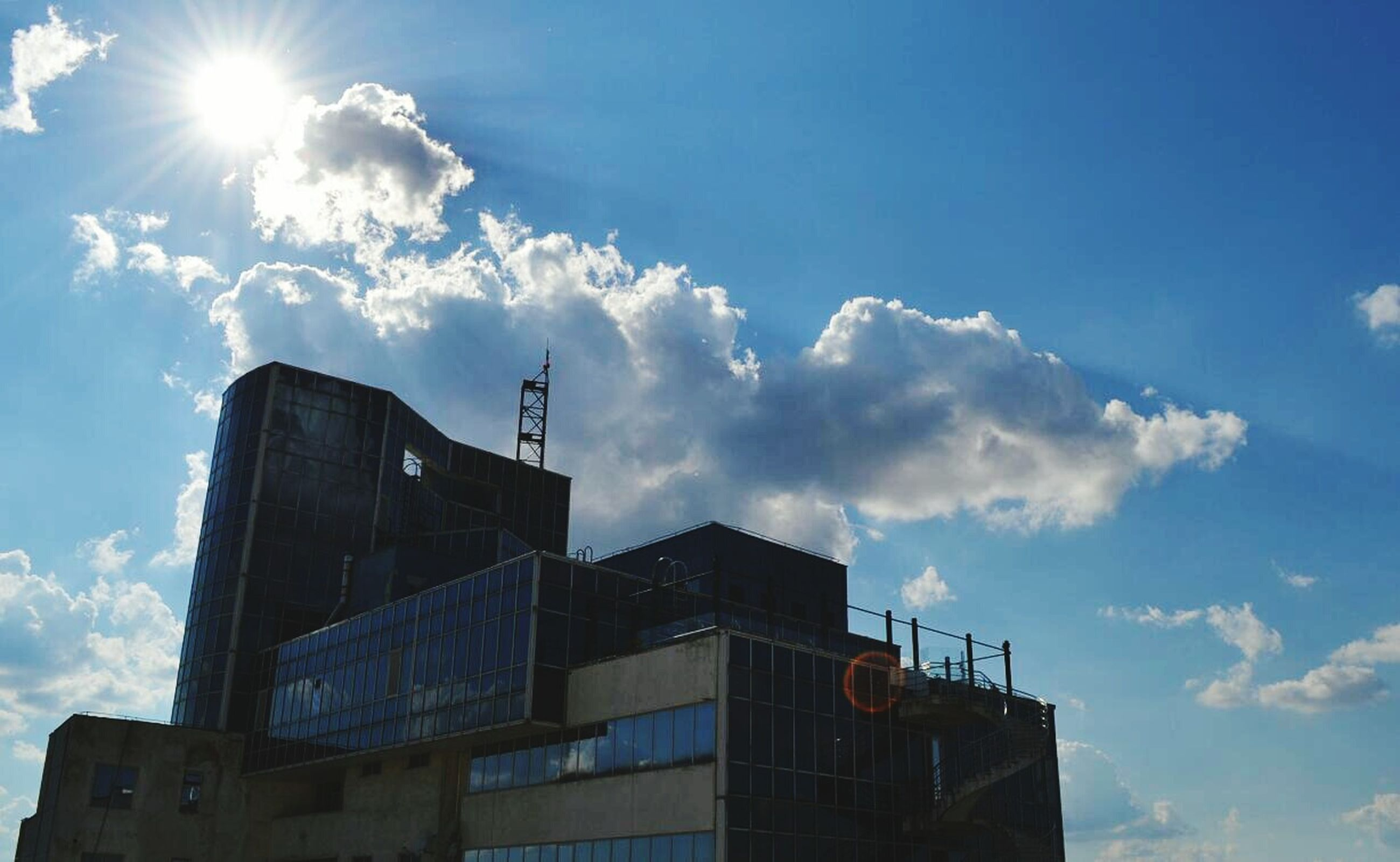 low angle view, building exterior, architecture, built structure, sun, sunbeam, sky, sunlight, blue, lens flare, sunny, building, day, cloud, city, cloud - sky, outdoors, no people, bright, high section
