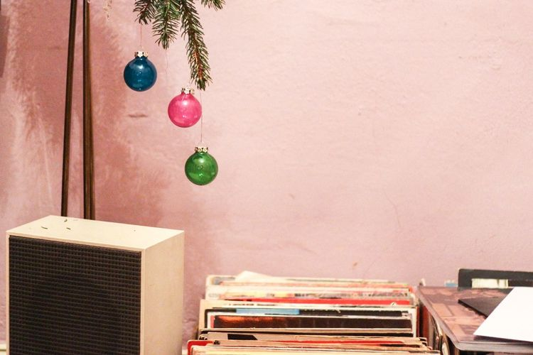 Christmas Baubles Hanging Over Documents At Table Against Wall